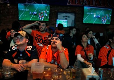 """In this Feb. 2, 2014 file photo, Denver Broncos fans watch their team play the Seahawks during the first half of the Super Bowl, inside Jackson's, a sports bar and grill in Denver. Senators from both parties warned the National Football League Thursday to get rid of a 4-decade-old TV """"blackout"""" rule or risk congressional action to restrict the league's lucrative antitrust exemption, which allows NFL teams to negotiate radio and television broadcast rights together. (AP Photo/Brennan Linsley, File)"""