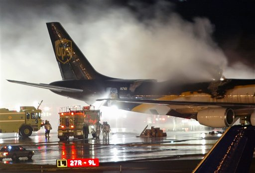 In this Feb. 8, 2006 file photo, firefighters battle a blaze onboard a UPS cargo plane at Philadelphia International Airport in Philadelphia. New U.S. government tests are raising concern that rechargeable lithium batteries carried as cargo on passenger airliners around the world are susceptible to fires or explosions that could destroy the planes. Yet U.S. and international officials have been slow to adopt safety restrictions that might affect both powerful industries that depend on the batteries and the airlines that profit from shipping them. The batteries are for products ranging from cellphones and laptops to hybrid cars.   (AP Photo/Joseph Kaczmarek, File)