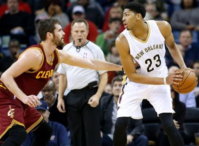 New Orleans Pelicans forward Anthony Davis (23) drives against Cleveland Cavaliers forward Kevin Love (0) during the first half of an NBA basketball game in New Orleans, Friday, Dec. 12, 2014. Davis left the game in the first quarter with an injury to the chest. (AP Photo/Jonathan Bachman)