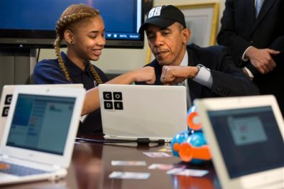"""President Barack Obama does a """"fist bump"""" with a Adrianna Mitchell during an """"Hour of Code"""" event in the Eisenhower Executive Office Building on the White House complex in Washington, Monday, Dec. 8, 2014, attended by  middle-school students from Newark, N.J. (AP Photo/Jacquelyn Martin)"""