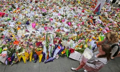 People come to lay flowers to pay respect to the shooting victims at a temporary memorial site close to the Lindt cafe in the central business district of Sydney, Australia, Wednesday, Dec. 17, 2014.  The siege ended early Tuesday with a barrage of gunfire that left two hostages and the Iranian-born gunman dead, and a nation that has long prided itself on its peace rocked to its core. (AP Photo/Rob Griffith)