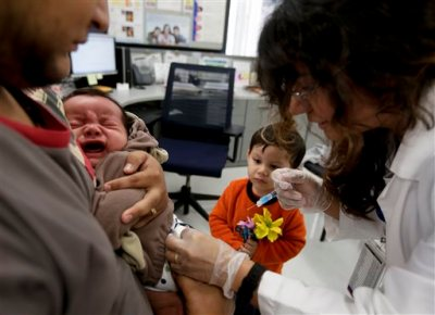 Julietta Losoyo, right, a Registered Nurse at the San Diego Public Health Center gives Derek Lucero a whooping cough injection while in his fathers Leonel's arms as his brother Iker, 2, looks on, Wednesday, Dec. 10, 2014 in San Diego. California is battling the worst whooping cough epidemic recorded in the state in seven decades.  State officials place much of the blame on a vaccine introduced in the 1990s that researchers say doesn't seem to be working as well as expected. (AP Photo/Chris Carlson)