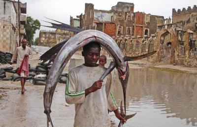 A Somali boy crosses a checkpoint with a fish on his head, in Mogadishu, Somalia (AP Photo)