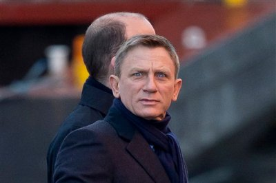 """Actor Daniel Craig jokingly pulls a face at photographers as he films a scene with Rory Kinnear, back obscured, on a canal for the new James Bond movie, """"SPECTRE,"""" in London, Tuesday, Dec. 16, 2014.  Filming is underway on the next James Bond movie, """"SPECTRE,"""" despite the leak of a draft script in a huge hack of material from Sony Pictures.  Daniel Craig and co-star Rory Kinnear took to a London canal in a speedboat on Tuesday for a waterborne sequence.  (AP Photo/Matt Dunham)"""