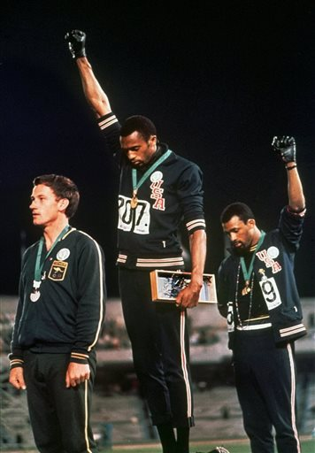In this Oct. 16, 1968, file photo, U.S. athletes Tommie Smith, center, and John Carlos stare downward while gesturing skyward during the playing of the Star Spangled Banner after Smith received the gold and Carlos the bronze for the 200 meter run at the Summer Olympic Games in Mexico City. Australian silver medalist Peter Norman is at left. Time will tell whether the ``hands-up'' gesture that five St. Louis Rams made during pregame introductions on Sunday, Nov. 30, 2014, will leave a lasting memory or simply go down as a come-and-go moment in the age of the 24-hour news cycle. Either way, it certainly isn't the first time high-profile athletes have used their platform to make political statements. (AP Photo/File)