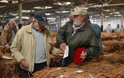 In this Nov. 18, 2014, photo, auctioneer Tripp Foy, at right, hands a tobacco purchase ticket to a buyer at an auction in Danville, Ky. Foy has been doing live tobacco auctions in Kentucky for four decades, and he is one of the last tobacco auctioneers in the country. (AP Photo/Dylan Lovan)