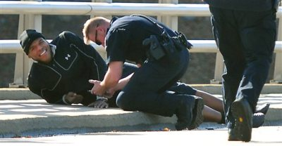 A Charlotte-Mecklenburg police officer tends to Carolina Panthers NFL football quarterback Cam Newton following a two-vehicle crash not far from the team's stadium in Charlotte, N.C., Tuesday, Dec. 9, 2014. (AP Photo/The Charlotte Observer, Todd Sumlin)