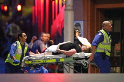 An injured hostage is wheeled to an ambulance after shots were fired during  a cafe  siege at Martin Place in the central business district of Sydney, Australia, Tuesday, Dec. 16, 2014. New South Wales state police would not say what was happening inside the cafe or whether hostages were being held. But television footage shot through the cafe's windows showed several people with their arms in the air.(AP Photo/Rob Griffith)