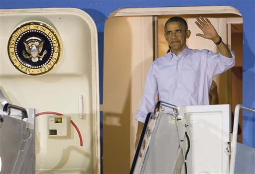President Barack Obama and the first family disembark Air Force One after arriving at Joint Base Pearl Harbor-Hickam for their annual family Christmas vacation Friday, Dec. 19, 2014, in Honolulu. The first family will be staying in Kailua, Hawaii. (AP Photo/Eugene Tanner)