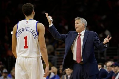 In this Dec. 1, 2014, photo, Philadelphia 76ers' Brett Brown, right, reacts to a call as Michael Carter-Williams looks on during an NBA basketball game against the San Antonio Spurs in Philadelphia. The winless Philadelphia 76ers are the worst team in the NBA and on another lengthy losing streak for the second straight season. (AP Photo/Matt Slocum)