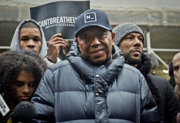 Rap music mogul Russell Simmons, center, and rapper Common, right, join a coalition of protest organizers at City Hall, Wednesday, Dec. 10, 2014, in New York. Rappers are joining activists to demand changes to policing and prosecution. (AP Photo/Bebeto Matthews)