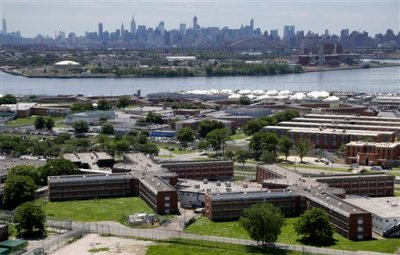 In this this June 20, 2014, file photo, the Rikers Island jail complex stands in the foreground with the New York skyline in the background. In the midst of heightened scrutiny to reform New York City's jails, reports of violence by guards against inmates reached an all-time high in 2014, according to documents obtained by The Associated Press. (AP Photo/Seth Wenig, File)