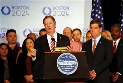As Boston Mayor Martin Walsh looks on, right, USOC Chairman of the Board Larry Probst speaks during a news conference in Boston Friday, Jan. 9, 2015 after Boston was picked by the USOC as its bid city for the 2024 Olympic Summer Games. (AP Photo/Winslow Townson)