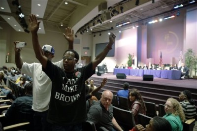 In this Sept. 9, 2014 file photo, Marurice Brown raises his arms during a public comments portion of a meeting of the Ferguson City Council, back right, in Ferguson, Mo.  Candidates for the first municipal election in Ferguson since a fatal police shooting brought the St. Louis suburb international notoriety face a filing deadline Tuesday, Jan. 20, 2015. Ferguson is nearly 70 percent black, all but one of its elected leaders is white. (AP Photo/Jeff Roberson, File)