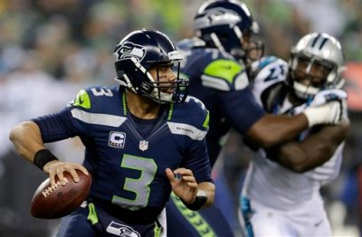 Seattle Seahawks quarterback Russell Wilson (3) scrambles against the Carolina Panthers during the first half of an NFL divisional playoff football game in Seattle, Saturday, Jan. 10, 2015. (AP Photo/John Froschauer)