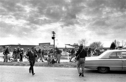 """In this March 7, 1965 file photo, John Lewis, center, of the Student Nonviolent Coordinating Committee, is forced to the ground by a trooper as state troopers break up the demonstration on what has become known as """"Bloody Sunday"""" in Selma, Ala. Supporters of black voting rights organized a march from Selma to Montgomery to protest the killing of a demonstrator by a state trooper and to improve voter registration for blacks, who are discouraged to register.  (AP Photo)"""