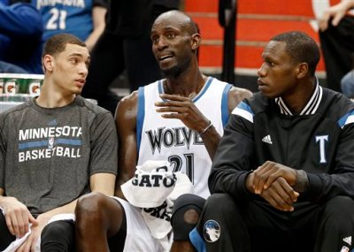 Minnesota Timberwolves' Kevin Garnett, center, chats on the bench with rookies Zach LaVine, left, and Andrew Wiggins in the first quarter of an NBA basketball game against the Washington Wizards, Wednesday, Feb. 25, 2015, in Minneapolis. (AP Photo/Jim Mone)