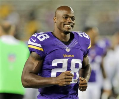 In this Aug. 8, 2014, file photo, Minnesota Vikings running back Adrian Peterson leaves the field after an NFL preseason football game against the Oakland Raiders in Minneapolis. A federal judge has cleared the way for Peterson to be reinstated. U.S. District Judge David Doty issued his order Thursday, Feb. 26, 2015, less than three weeks after hearing oral arguments. (AP Photo/Jim Mone, File)