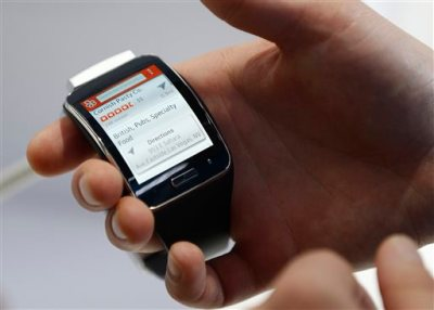 In this Jan. 6, 2015 file photo, an employee demonstrates the Samsung Gear S smartwatch at the Samsung booth during the International CES in Las Vegas. (AP Photo/John Locher, File)