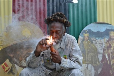 "In this Aug. 28, 2014 file photo, legalization advocate and reggae legend Bunny Wailer smokes a pipe stuffed with marijuana during a ""reasoning"" session in a yard in Kingston, Jamaica. Jamaica lawmakers on Tuesday, Feb. 24, 2015, passed an act to decriminalize small amounts of pot and establish a licensing agency to regulate a lawful medical marijuana industry on the island. (AP Photo/David McFadden, File)"