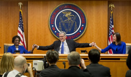"""Federal Communication Commission (FCC) Chairman Tom Wheeler, center, joins hands with FCC Commissioners Mignon Clyburn, left, and Jessica Rosenworcel, before the start of their open hearing in Washington, Thursday, Feb. 26, 2015. Internet service providers like Comcast, Verizon, AT&T, Sprint and T-Mobile would have to act in the """"public interest"""" when providing a mobile connection to your home or phone, under new rules being considered by the Federal Communications Commission. The rules would put the Internet in the same regulatory camp as the telephone, banning providers from """"unjust or unreasonable"""" business practices. (AP Photo/Pablo Martinez Monsivais)"""