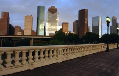 The Houston skyline looms over a brick sidewalk on the Sabine Street bridge over Buffalo Bayou in this July 2004 photo. (AP Photo/Pat Sullivan)