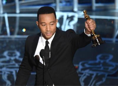 """John Legend accepts the award for best original song in a feature film for """"Glory"""" from """"Selma"""" at the Oscars on Sunday, Feb. 22, 2015, at the Dolby Theatre in Los Angeles. (Photo by John Shearer/Invision/AP)"""