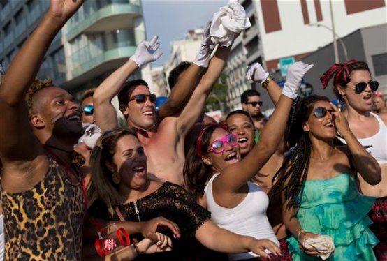 Revelers dance and sing during the Banda de Ipanema carnival block party in Rio de Janeiro, Brazil, Saturday, Feb. 14, 2015. The Banda de Ipanema is one of the largest block parties of Rio de Janeiro, and is celebrating it's 50th anniversary. The five days of over-the-top parades and raucous, alcohol-soaked street parties that make up Rio de Janeiro's world-famous Carnival celebrations kicked off Friday. (AP Photo/Silvia Izquierdo)