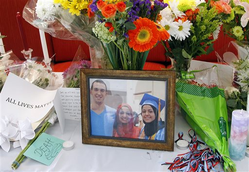 A makeshift memorial appears on display, Wednesday, Feb. 11, 2015, at the University of North Carolina School of Dentistry in Chapel Hill, N.C., in remembrance of Deah Shaddy Barakat, 23, Yusor Mohammad, 21, and Razan Mohammad Abu-Salha, 19, who were killed on Tuesday. Craig Stephen Hicks, 46, has been charged with three counts of first-degree murder in the case. (AP Photo/The News & Observer, Chris Seward) MANDATORY CREDIT, TV OUT