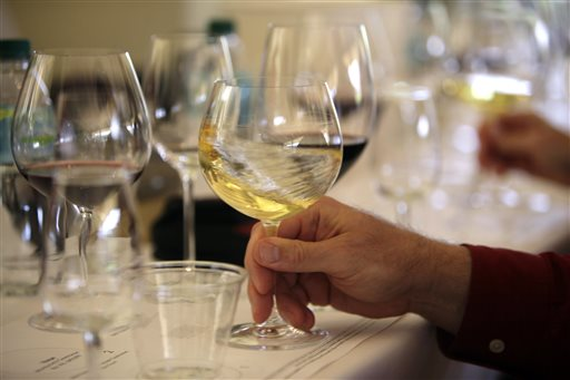 "File - In this May 20, 2009 file photo a glass of white wine is swirled during a tasting in Oakville, Calif. More than two dozen California vintners are facing a lawsuit claiming their wines contain dangerously high levels of arsenic. The industry group Wine Institute dismissed the allegations as ""false and misleading."" (AP Photo/Eric Risberg, File)"