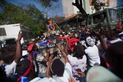 Protesters burn a Dominican flag in front of the country's consulate during an anti-Dominican Republic protest in Port-au-Prince, Haiti, Wednesday, Feb. 25, 2015. Protesters outraged over a Feb. 11 lynching of a young man of Haitian descent in the Dominican city of Santiago are demanding the neighboring country respect the human rights of Haitians. (Dieu Nalio Chery/AP)