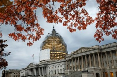 In this Nov. 13, 2014 file photo, the Capitol Dome is surrounded by scaffolding for a long-term repair project, and the last of autumn's colorful leaves frame the Capitol in Washington. Americans' confidence in all three branches of government is at or near record lows, according to a long-running and widely respected survey that's measured Americans' attitudes on the subject over the last 40 years. The 2014 General Social Survey finds only 23 percent of Americans have a great deal of confidence in the Supreme Court, 11 percent in the executive branch and only 5 percent have a lot of confidence in Congress. By contrast, half have a great deal of confidence in the military. (AP Photo/J. Scott Applewhite, File)