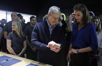 Apple CEO Tim Cook, left, and Christy Turlington Burns, founder of Every Mother Counts, look at the new Apple Watch in the demo room after an Apple event on Monday, March 9, 2015, in San Francisco. (AP Photo/Eric Risberg)