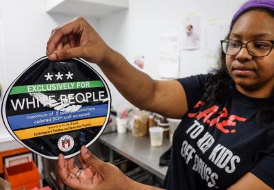 """April Jensen, an employee at Sugar Mama's holds a sticker that the business found on the front of their store in Austin, Texas, Wednesday, March 18, 2015. Employees at several businesses in Austin have found stickers saying """"exclusively for white people"""" placed on their windows, sparking an investigation into their origin and condemnation from the mayor. A city spokesman says city officials along with the Austin Police Department are investigating the stickers' origin. (AP Photo/Austin American-Statesman, Rodolfo Gonzalez)"""