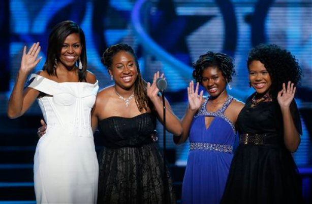 First Lady Michelle Obama, left, waves while standing on stage with Making A Difference award winners, from left, Kaya Thomas, Chental-Song Bembry and Gabrielle Jordan during a taping of the Black Girls Rock award ceremony at the New Jersey Performing Arts Center, Saturday, March 28, 2015, in Newark. (AP Photo/Julio Cortez)