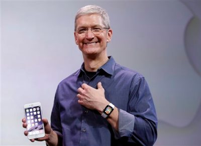 In this Sept. 9, 2014 file photo, Apple CEO Tim Cook, holding an iPhone 6 Plus and wearing an Apple Watch, discusses the new products during an event in Cupertino, Calif.  Cook has hinted the Apple Watch will be as game-changing as Apple's revolutionary iPhones and iPads, which have become indispensable accessories for millions around the globe. (AP Photo/Marcio Jose Sanchez, File)