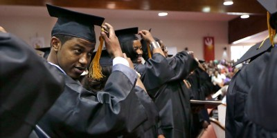In this May 5, 2014 photo, Krishaun Branch, left, moves the tassel on his mortarboard to the left side after graduating from Fisk University in Nashville, Tenn. Branch comes from Englewood, the often dangerous South Side neighborhood that's home to the first Urban Prep. (AP Photo/Mark Humphrey)