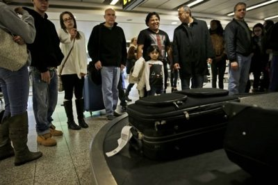 In this Nov. 25, 2014, file photo, travelers wait to claim their baggage at LaGuardia Airport in New York. An annual report being released Monday, April 13, 2015, states that government data shows more flights are late, more bags are getting lost, and customers are lodging more complaints about U.S. airlines. (AP Photo/Seth Wenig, File)