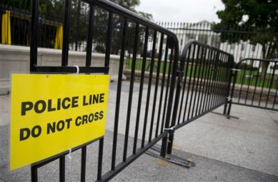 """In this Oct. 3, 2014, file photo, a temporary barrier marked with a sign """"Police Line Do Not Cross"""" is seen along Pennsylvania Avenue in front of the White House in Washington. The Secret Service has placed a high-ranking supervisor on administrative leave and suspended the supervisor's security clearance after what it calls """"allegations of misconduct and potential criminal activity."""" (AP Photo/Carolyn Kaster, File)"""