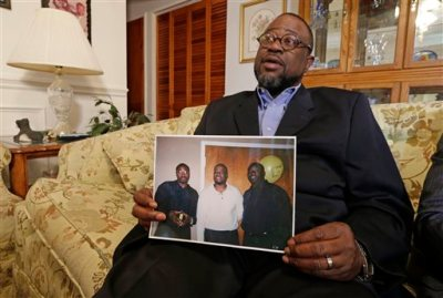 Anthony Scott holds a photo of himself, center, and his brothers Walter Scott, left, and Rodney Scott, right, as he talks about his brother at his home near North Charleston, S.C., Wednesday, April 8, 2015. Walter Scott was killed by a North Charleston police officer after a traffic stop on Saturday. The officer, Michael Thomas Slager,  has been charged with murder. (AP Photo/Chuck Burton)