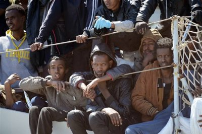 Migrants wait to disembark from the Italian Navy vessel 'Chimera' in the harbor of Salerno, Italy, Wednesday, April 22, 2015. Italy pressed the European Union on Wednesday to devise concrete, robust steps to stop the deadly tide of migrants on smugglers' boats in the Mediterranean, including setting up refugee camps in countries bordering Libya. Italian Defense Minister Roberta Pinotti also said human traffickers must be targeted with military intervention. (AP Photo/Francesco Pecoraro)