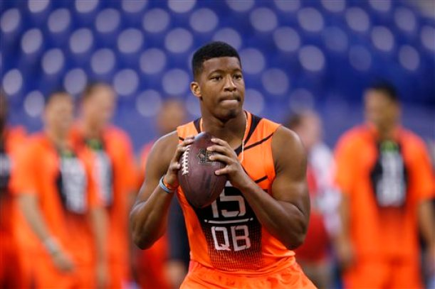 In this Feb. 21, 2015, file photo, Florida State quarterback Jameis Winston runs a drill at the NFL football scouting combine in Indianapolis. While 26 draft-eligible players have accepted invitations from the NFL to attend the proceedings later this month, Winston and Marcus Mariota are not among them. The two most recent Heisman Trophy winners and highest-profile players in this year's crop have opted to stay home with their families for the April 30-May 2 draft. (AP Photo/Julio Cortez, File)