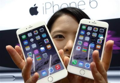 In this Sept 19, 2014 file photo, a customer shows off the new Apple iPhone 6, right, and 6 Plus at a store in Tokyo. Apple sold 61 million iPhones in the first three months of 2015, or 40 percent more than in the same period a year ago. That represented about two-thirds of its $58 billion in revenue. (AP Photo/Shizuo Kambayashi, File)