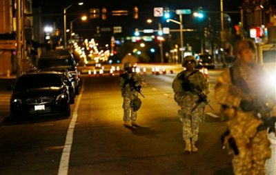 Members of the National Guard walk along North Avenue near where Monday's riots occurred following the funeral for Freddie Gray, after a 10 p.m. curfew went into effect Wednesday, April 29, 2015, in Baltimore. (AP Photo/David Goldman)