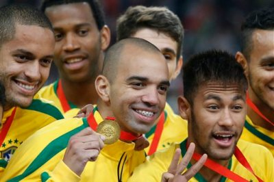 In this Saturday, Oct. 11, 2014 photo, Brazil's Diego Tardelli, center, celebrates with Neymar, right, and his other teammates after winning a Brazil vs. Argentina friendly soccer match at the Bird's Nest National Stadium in Beijing, China. Striker Tardelli this year became the first player from a Chinese club to be picked for Brazil's national team. He was considered one of the top prospects in the country when he made the move to Shandong Luneng instead of taking up other deals that could have increased his profile. (AP Photo/Ng Han Guan)