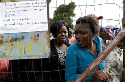 A women queues for food at a temporary refugee camp for foreign nationals fleeing, in east of Johannesburg, South Africa, Monday, April 20, 2015. A total of seven people have died in attacks on immigrants in South Africa in the past week bringing the South African president to postpone a key ceremony, his office said Monday. The anti-immigrant violence has been in specific areas of Durban and Johannesburg. Six people died in attacks in the coastal city of Durban, where looters broke into shops owned by immigrants, police said. The violence has since subsided. (AP Photo/Themba Hadebe)