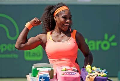Serena Williams poses with a cake celebrating her 700th career win after she defeated Sabine Lisicki during their quarterfinal match at the Miami Open tennis tournament, Wednesday, April 1, 2015, in Key Biscayne, Fla. Williams won the match 7-6 (4), 1-6, 6-3. (AP Photo/Lynne Sladky)