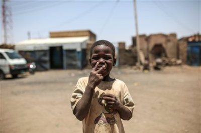 In this picture taken on Tuesday, April 14, 2015, a Sudanese boy gestures to the camera for a smoke, outside his home in Izba, an impoverished neighborhood on the outskirts of Khartoum, Sudan. Izba is one sign of how the constant internal wars, under Sudan's President Omar al-Bashir, have shaped, Khartoum. Before al-Bashir came to power, Izba was home to a community of Arab tribesmen who had settled here to be close to the capital. But through the 1990s and 2000s, it swelled with Sudanese fleeing war zones around the country. Now 70,000 people live crammed into Izba, an area of about a square mile. (AP Photo/Mosa'ab Elshamy)