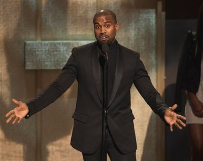In this Jan. 24, 2015, file photo, BET Honoree Kanye West accepts the Visonary Award at the BET Honors 2015 at Warner Theater in Washington. West on Tuesday, April 7, 2015, settled a lawsuit filed by a paparazzo who the rapper attacked outside a Los Angeles International Airport terminal in 2013. Daniel Ramos' attorney Gloria Allred wrote in a statement that  the suit was settled in part after West apologized to her client and the pair shook hands.  (Photo by Kevin Wolf/Invision/AP, File)