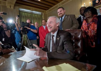 Arkansas Gov. Asa Hutchinson signs a reworked religious freedom bill into law after it passed in the House at the Arkansas state Capitol in Little Rock, Ark., Thursday, April 2, 2015. (AP Photo/Brian Chilson)